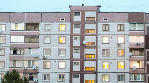 Multi-storey houses, in apartments that light up windows. Timelapse.