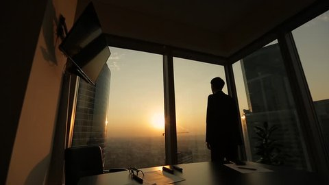 Businessman walking to windows in office and looks thoughtfully into the distance at sunset. Dolly.