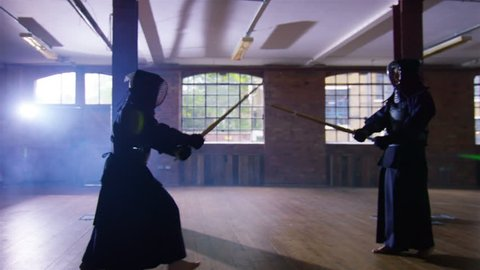 4K Japanese kendo fighters with bamboo swords competing in dark industrial building. Shot on RED Epic.