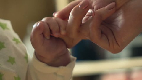 Mother holding little baby hand, super slow motion