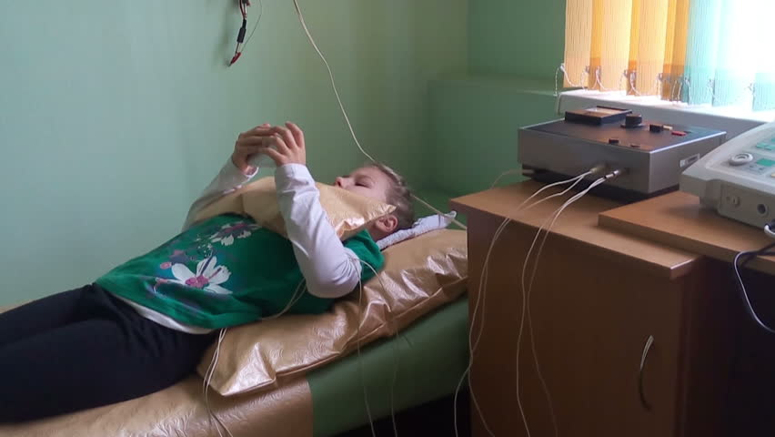 ST. PETERSBURG, RUSSIA - CIRCA OCT, 2015: Young ill child has electrophoresis procedure while lays sofa and plays mobile phone. Ambulatory treatment is in Russian children's polyclinic center.  | Shutterstock HD Video #12430463