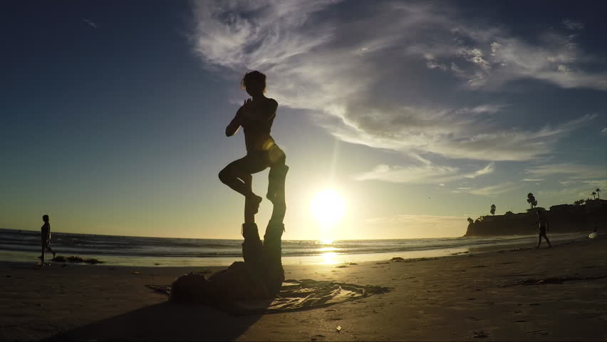 Beach sunset acroyoga routine 60fps. Silhouette beauty shot.   Shutterstock HD Video #12454493