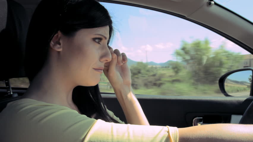 heartbroken woman crying desperate while driving car