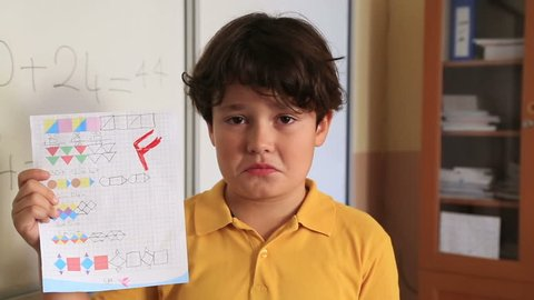 Brat schoolboy  holding school paper with F grade