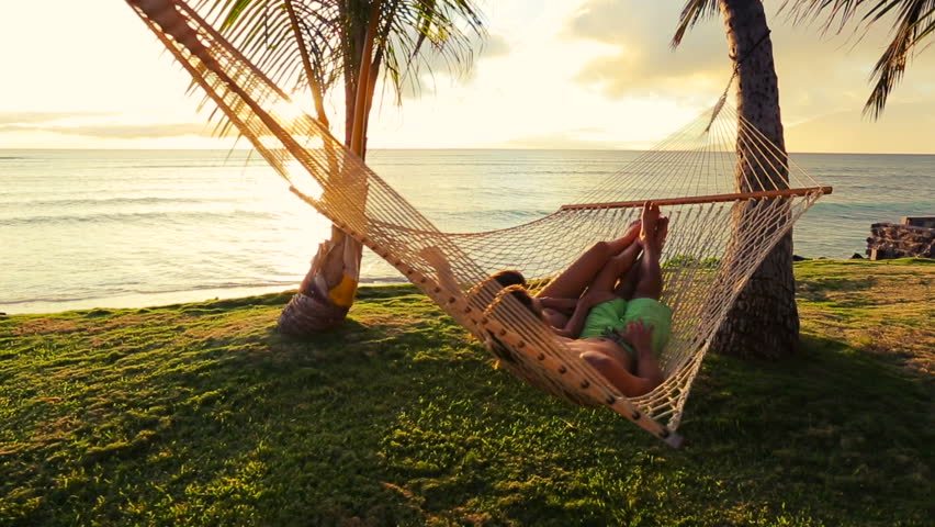 Romantic couple relaxing in tropical hammock at sunset for Tropical vacations for couples