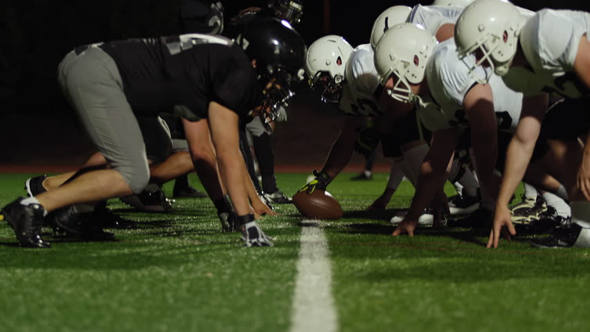 A football player gets tackled on his way to the end zone at night | Shutterstock HD Video #12495863