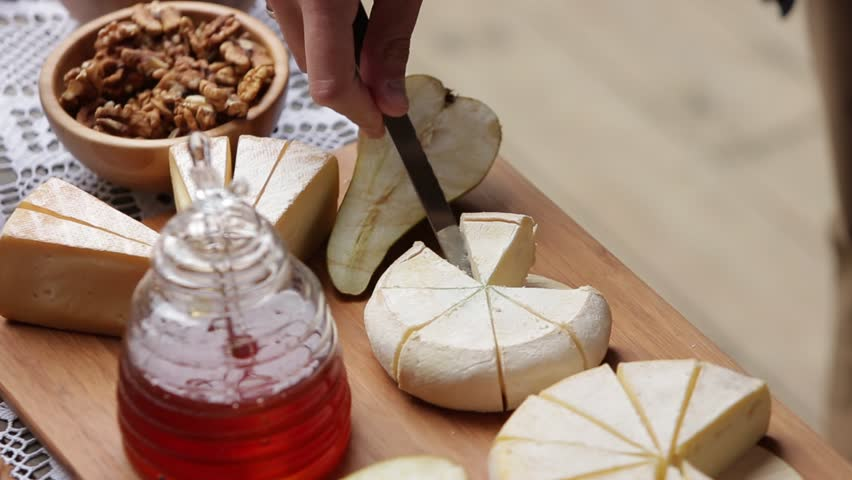 Male hand cuts and takes a piece of cheese with a beautiful table with snacks
