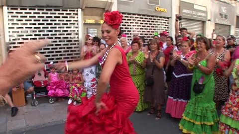 MALAGA, SPAIN - AUGUST, 14: People dancing in flamenco style dress and getting fun at the Malaga August Fair, on August, 14, 2014 in Malaga, Spain