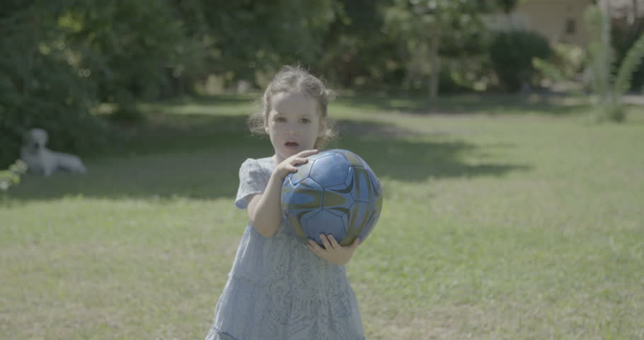 A little girl wearing a dress playing with a blue ball | Shutterstock HD Video #12530243