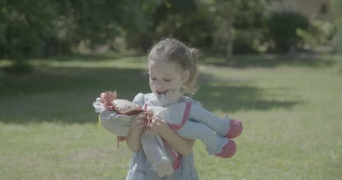 A little girl playing with a doll outdoors on a lawn