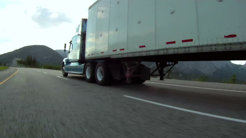 Vehicle pov shot of semi trailer truck traffic on highway