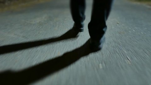 man walking alone at night in the park. shadow silhouette of person. spooky night scenery background