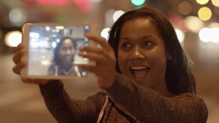 Happy black women using tablet pc to take a selfie in the city at night | Shutterstock HD Video #12570773