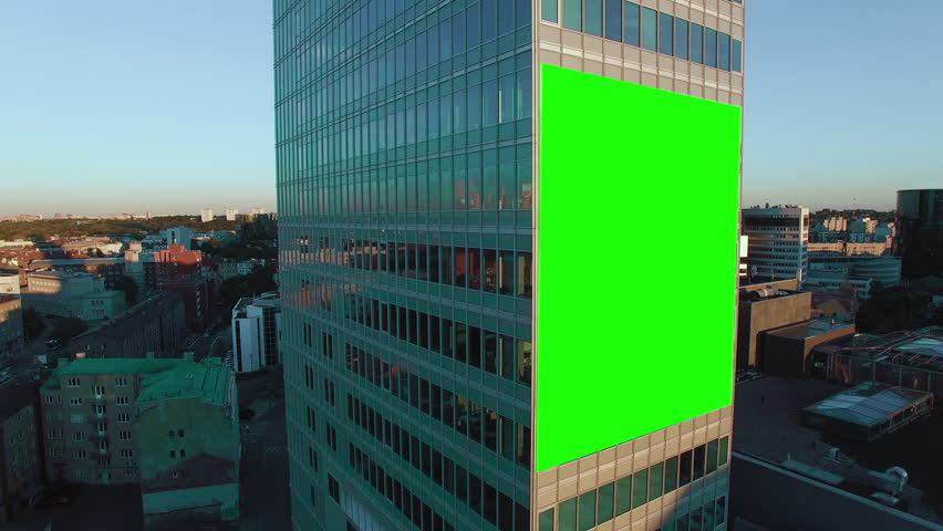 Aerial Orbit Shot of Glass Office Building With Green Screen Mock-up of Billboard in Business District.