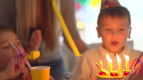 Little boy blows out candles on birthday cake at party, Happy big family celebrating birthday of little kid. slow motion 240 fps, high speed camera, HD 1080p