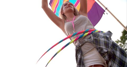 Girl hula-hooping with two hoops at a festival, slow motion