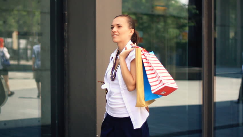 Woman with shopping bags walking by the shop window, camera stabilizer shot, slow motion