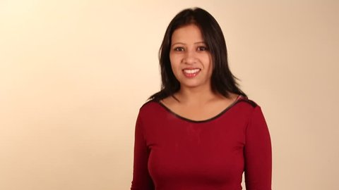 Indian Girl Wearing Red Dress Showing Victory Sign And Thumbs Up In Studio Against A White