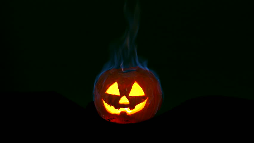 burning halloween pumpkin in the dark 4k stock footage clip - Halloween Background Video