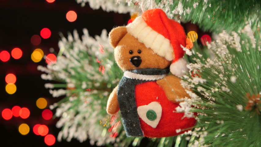christmas decoration a toy teddy bear on christmas tree bokeh light on black background garland cam moves to the left stock footage video 12656093 - Bear Christmas Tree