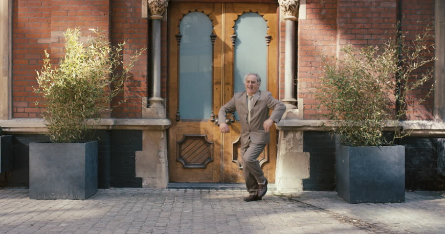 Happy elderly dancer man wearing suit in front of apartment funky street dancing freestyle in the city