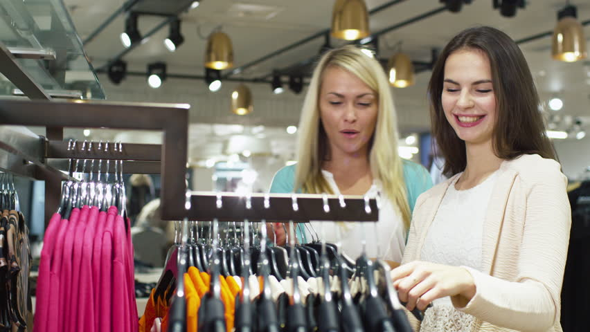 aeb36ae2057 Two happy young girls are shopping clothes in a department store. Shot on  RED Cinema Camera in 4K (UHD).