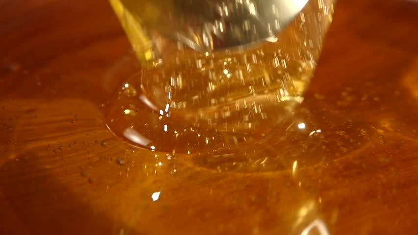 Taking honey by using metal spoon in wooden bowl, slow motion, macro | Shutterstock HD Video #12670463