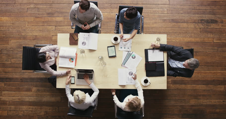 Top view diverse business people meeting at boardroom table discussing financial report using graphs and big data in trendy shared office space   Shutterstock HD Video #12707138