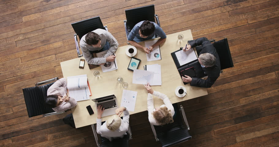 Top view diverse business people meeting at boardroom table discussing financial report using graphs and big data in trendy shared office space | Shutterstock HD Video #12707153