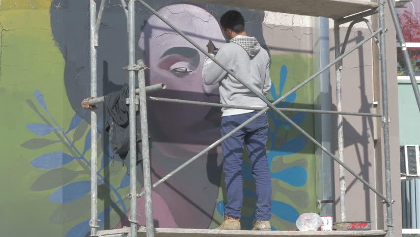 Talented Young Man Standing On Scaffold And Painting Mural Or Graffiti With  Brush. Performance, Part 75