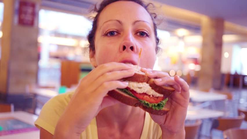 Happy woman eats fresh delicious sandwich in bakery