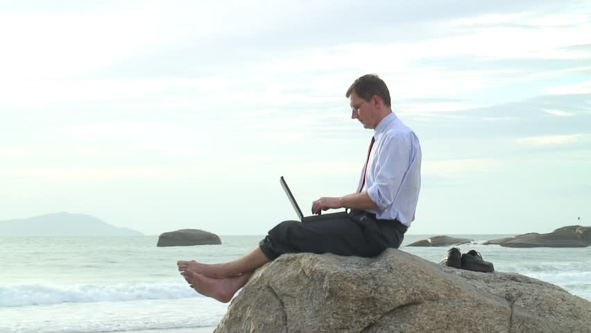 Businessman working with laptop while sitting on a rock on the beach.