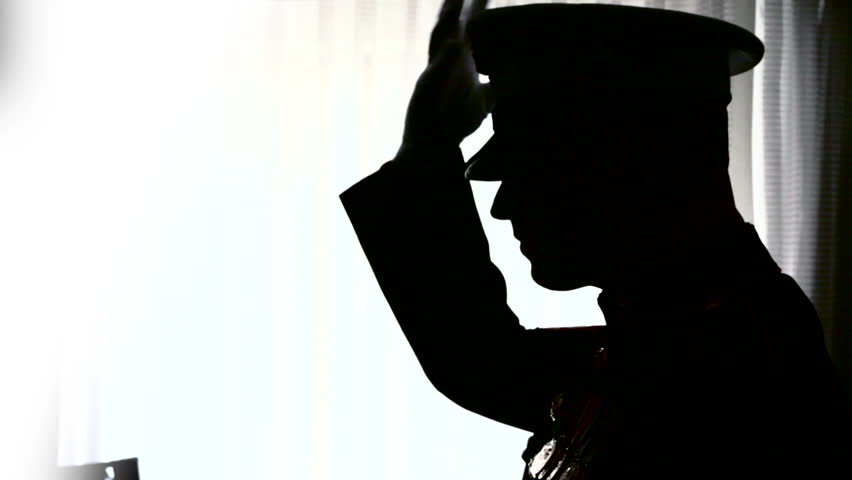 Silhouette of Marine putting on his hat.
