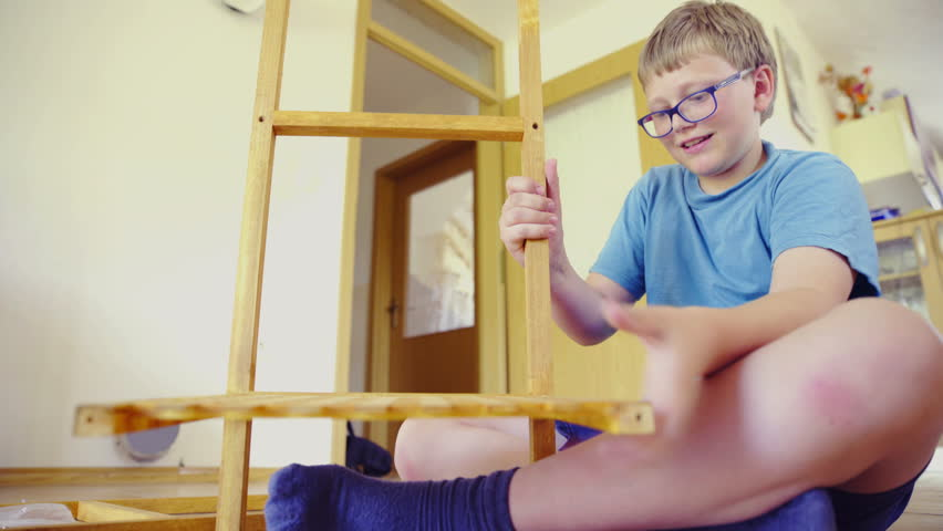 Boy sit on floor and put together a tower 4K. Low angle view of young person in blue shirt and wearing glasses screwing first shelf on wooden frame for shelves tower in living room. | Shutterstock HD Video #12771587