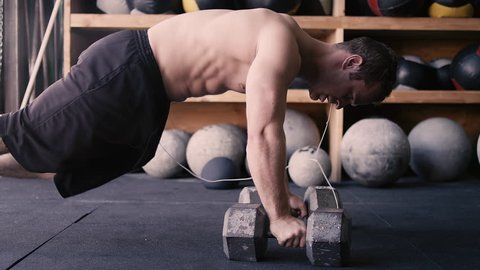 A fit young man doing push-ups with dumbbells in a gym
