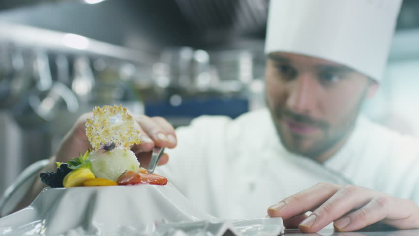 Happy professional chef in a commercial kitchen is garnishing ice cream dessert with strawberry. Shot on RED Cinema Camera in 4K (UHD).