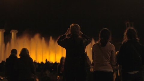 People watching and recording with their phones and cameras the lightshow of the Magic Fountain of Montjuic, Barcelona, Spain. (Barcelona, Spain - April 2015)