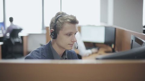 Young man call center agent speaking with costumer