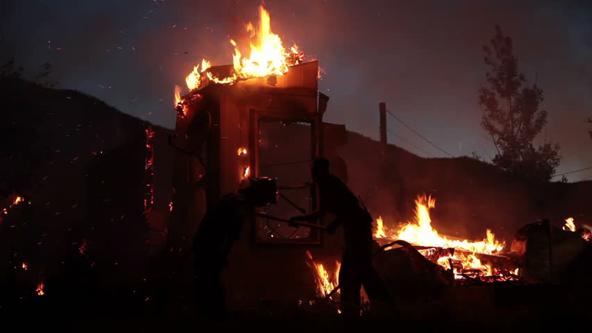 House fire during the night with flames burning and destroying the entire home. Two firemen work as silhouettes trying to control the blaze.