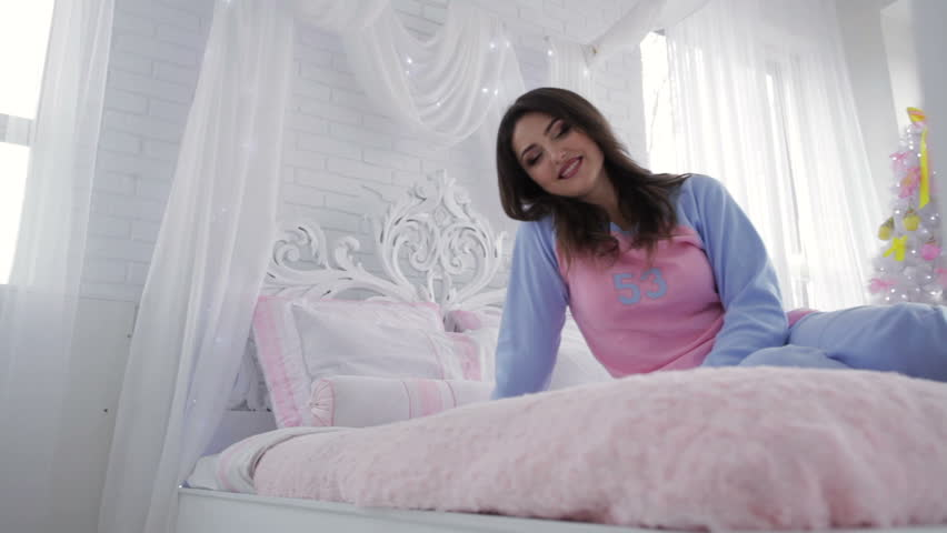 smiling girl with pillows sitting on bed near firtree hd stock footage clip