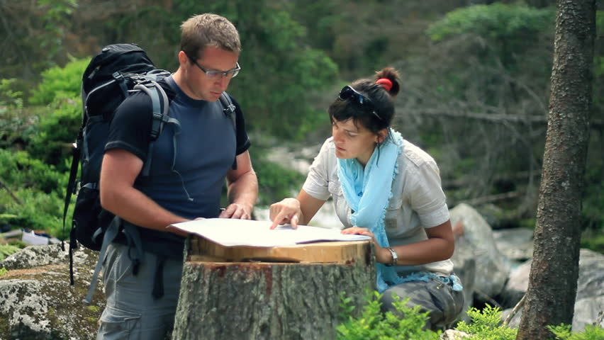 A couple with map and compass in the forest