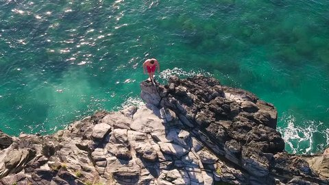 Cliff Jumping into Ocean. Aerial View Slow Motion. Young Man Jumps off Cliff Into Blue Ocean. Summer Extreme Sports Outdoor Lifestyle.