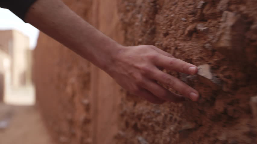 Man walks and grazes hand on stone wall. Shot in Morocco. | Shutterstock HD Video #12874283