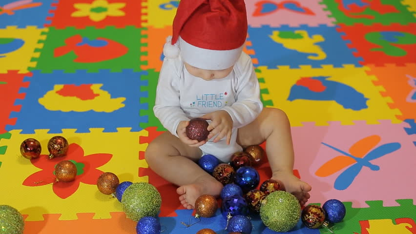 ... Happy Baby with Santa cap playing with Christmas red decorations ... e3d3f36005f