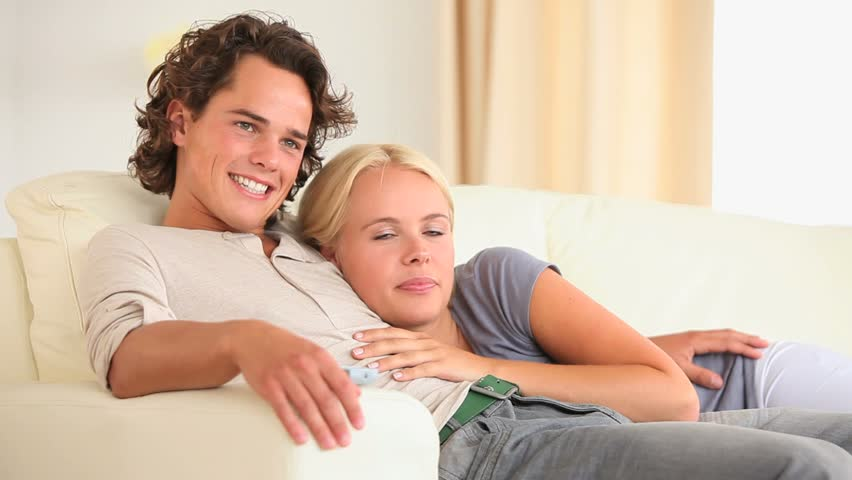Happy couple on a sofa watching TV in the living room