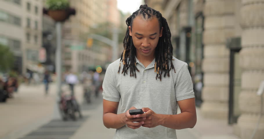 Young man walking New York City street texting cell phone   Shutterstock HD Video #12917282