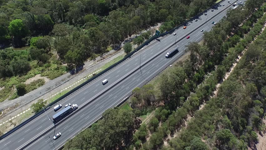 Aerial view freight semi trailer lori trucks, vehicles and cars traveling on country outback, rural High speed freeway or motorway driving scenes on open road on Gateway Motorway M1 Australia.