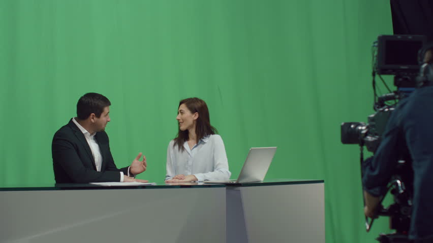 Backstage footage of male and female broadcasters who sit at a table and talk on a mock-up green screen in the background. Shot on RED Cinema Camera in 4K (UHD). | Shutterstock HD Video #12942743