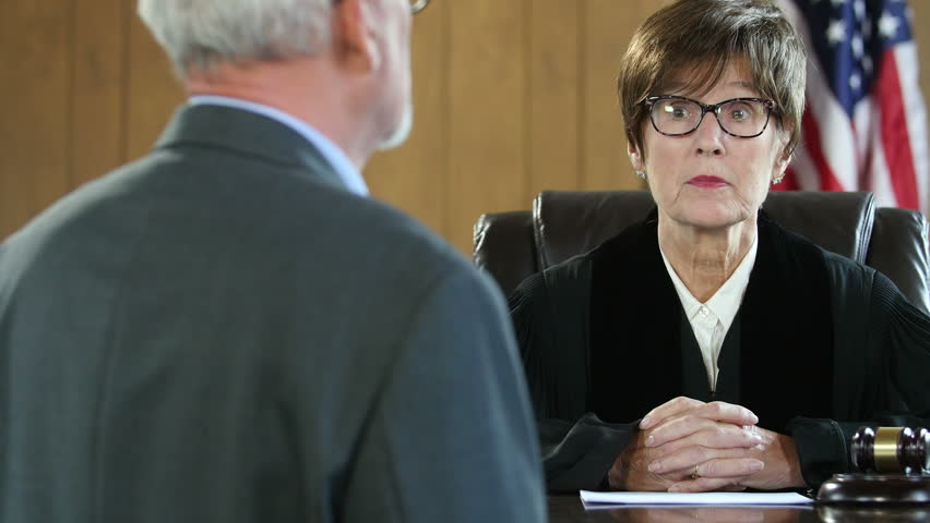 Female judge with male attorney in courtroom