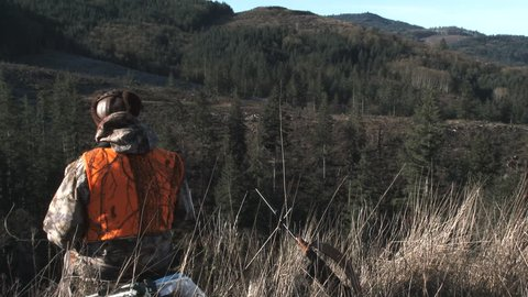Unrecognizable hunter looking out over forest with binoculars during hunting season in Washington State.